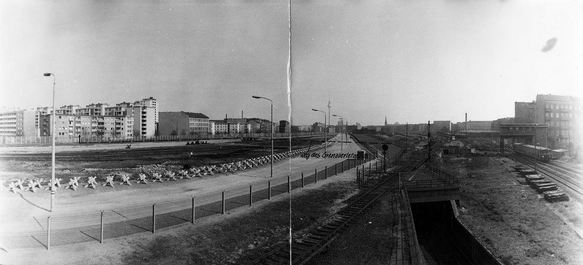 [Das sichchwarzweiße Lichtbild zeigt die Grenzbefstigungsanlagen in Berlin-Mitte. Darauf wurde mittels gestrelter Linie der 'Weg des Grenzhverletzers' eingezeichnet.]