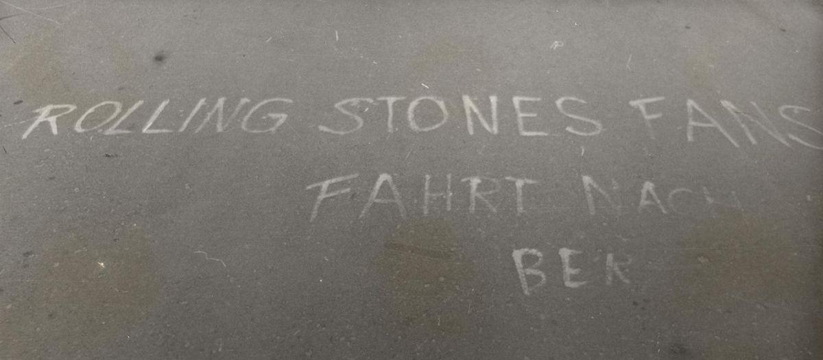 Schwarzweiß Aufnahme von der Fahrbahn mit der Aufschrift: 'Rolling Stones Fans fahrt nach Ber'