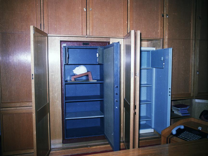 Die Aufnahme zeigt eine Front von Einbauschränken hinter dem ehemaligen Schreibtisch von Erich Mielke, von denen zwei geöffnet sind.