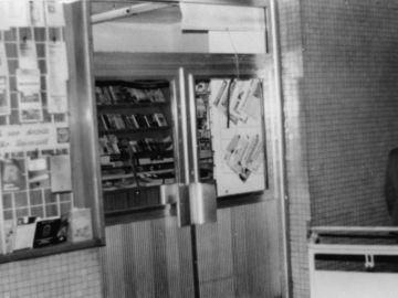 Als Teil einer Fotodokumentation ist auf dem schwarz-weißen Lichtbild die äußere Flügeltür eines Imbiss auf dem Bahnhof zu sehen. Die Fenster sind eingeschlagen.