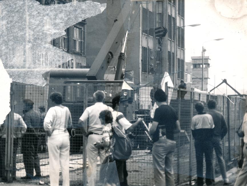 Vor einem Bauzaun am Union-Verlagsgebäude stehen Schaulustige. Dahinter steht ein Kran und versetzt Mauerelemente. Das Foto war mehrfach zerrissen worden und ist nun manuell rekonstruiert. Dennoch fehlt auf der rechten Seite ein Stück Bildinformation, direkt daneben wurde (durch das Reißen) die Fotoschicht halb abgelöst.