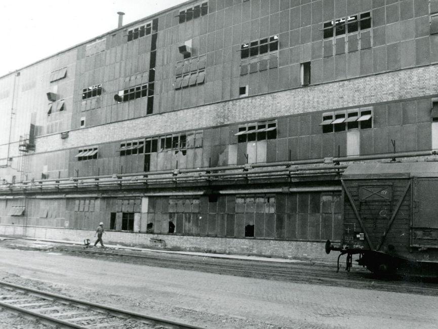 [Auf der schwarz-weiß Fotografie ist ein mehrstöckiges Industriegebäude zu erkennen. Das Gebäude besteht aus vielen Fenstern, einige stehen offen und einige sind beschädigt. Über dem ersten Stock verlaufen einige Rohre parallel. Davor ist ein Mann mit einem Schutzhelm zu sehen. Er läuft in Richtung eines Güterwagons, der rechts vor dem Gebäude steht. Vor dem Gebäude verlaufen zwei Eisenbahnschienen.]