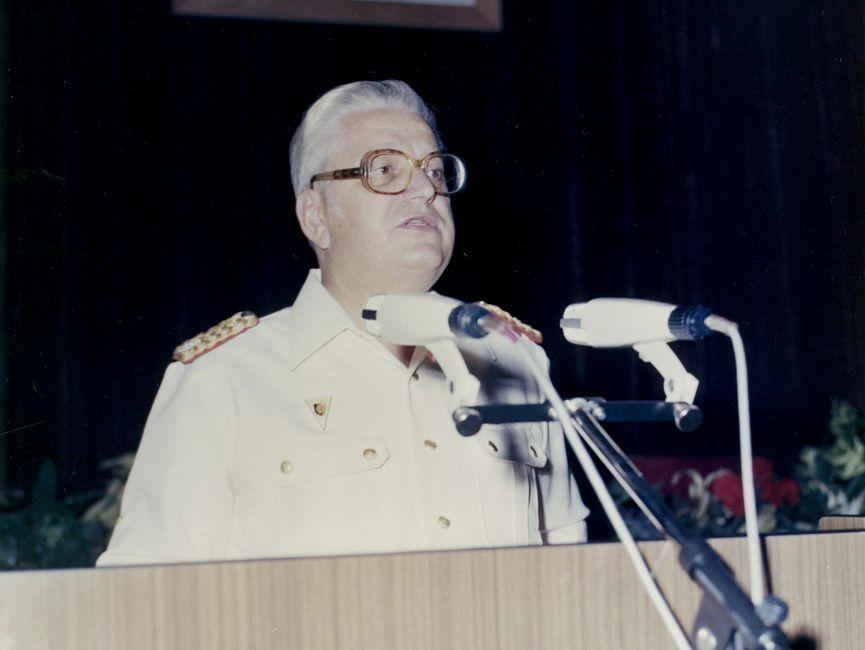 Willi Pösel in weißer Uniform an einem Rednerpult mit Mikrofonen.