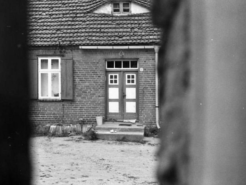 Durch einen Spalt hindurch wurde die Eingangstür des Fachwerkhauses abfotografiert. Daneben ist ein weiteres Fenster. Es handelt sich um ein schwarz-weißes Lichtbild.