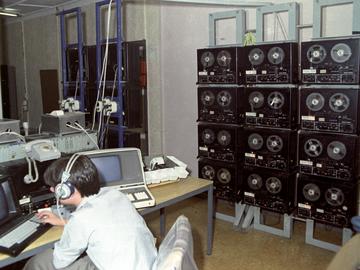 [Im Vordergrund des farbigen Lichtbildes sitzt ein junger Mann im Hemd mit Kopfhörern vor einem Schreibtisch mit zwei Computern. Beide Bildschirme sind schwarz. Auf einem Tonbandgerät, das mittig zwischen beiden Rechnern steht, steht ein Tischtelefon. Rechts von ihm sind drei graue Metallständer, die mit jeweils vier Tonbandgeräten bestückt sind. Im Hintergrund sind weitere Gerätschaften zu sehen.]
