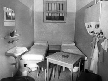 Einfach eingerichtete Gefängniszelle für zwei Personen. Die gesamte Einrichtung wirkt sorgfältig platziert.