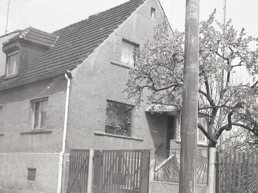 [Die schwarz-weiß Fotografie wurde von der Beifahrerseite eines parkenden Fahrzeuges geschossen. Links auf der Fotografie ist ein Einfamilienhaus an einer Straße zu sehen. Auf dem Grundstück, rechts neben dem Haus, steht ein Kirschbaum. Angrenzend an den Kirschbaum beginnt ein neues Grundstück.]