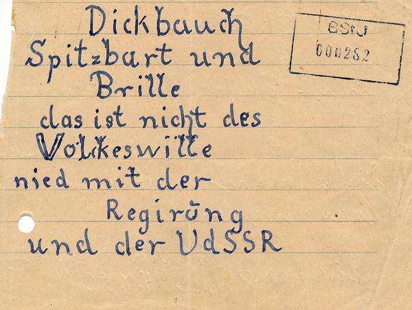Auf diesem Bild befindet sich eine Losung mit dem Schriftzug:  'Dickbauch, Spitzbart und Brille das ist nicht des Volkeswille nied mit der Regirung und der UdSSR.'