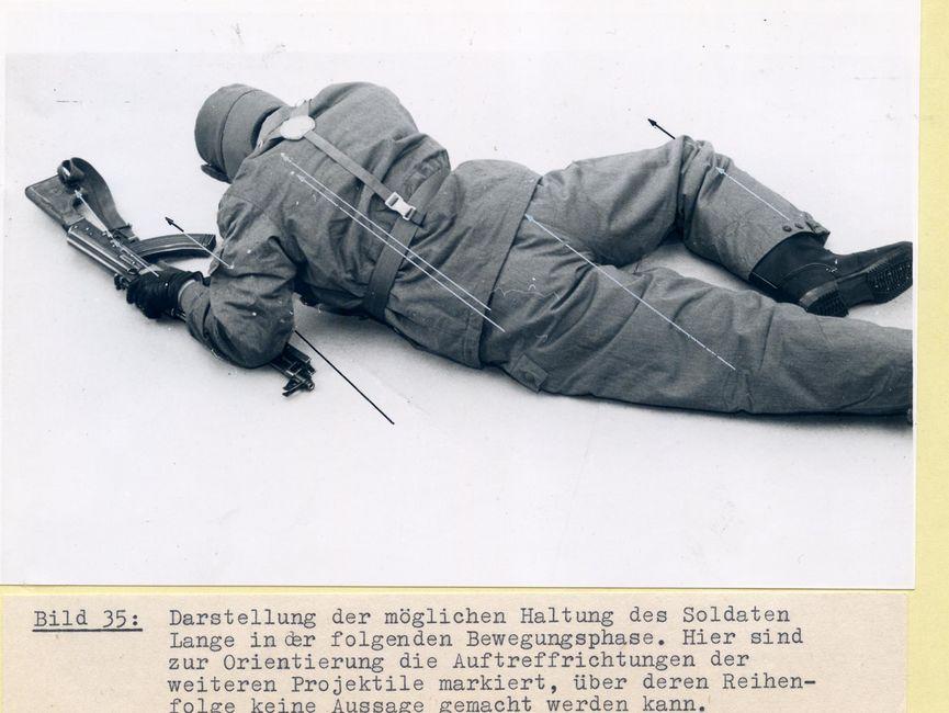 [Auf den beiden schwarzweißen Fotos liegt eine Person, sich mit den Armen hoch drückend, leicht seitlich auf dem Bauch und dreht dabei den Rücken zur Kamera. Dabei ist sie in Uniform und Koppel der NVA-Grenztruppen gekleidet und trägt auch die Fellmütze. Das rechte Bein ist angewinkelt, mit dem linken Arm stützt sie sich auf der Maschinenpistole auf. Dabei ist das Lauf unter dem Unterarm, die restliche Hälfte der Waffe liegt in Richtung des Kopfes und damit von der Kameraposition weg. Es sind feine schwarze und graue Pfeile zu sehen, die die Auftreffrichtungen der Projektile beim Soldaten Lange markieren.]