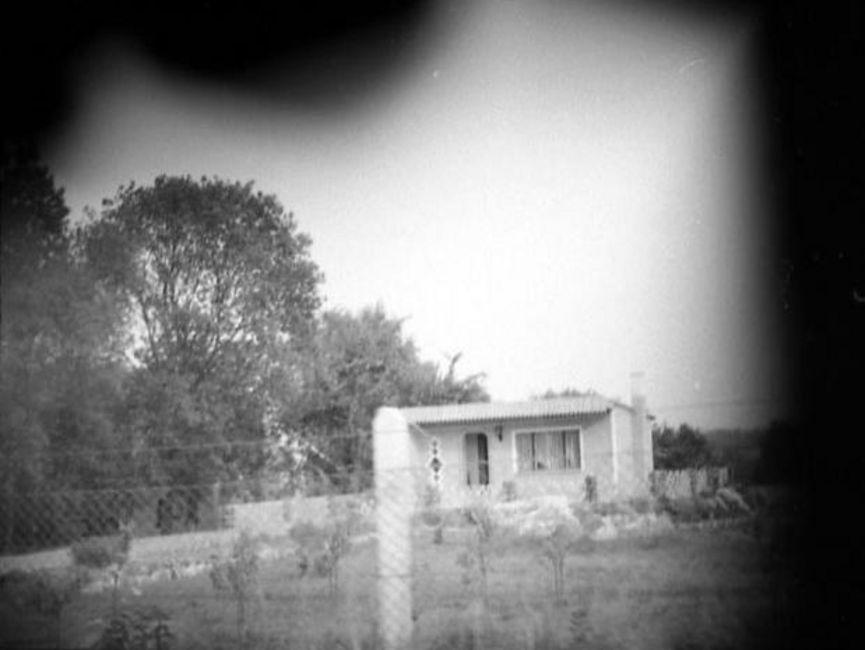 Auf dem schwarz-weißen Lichtfoto wurde ein Bungalow auf einer Anhöhe abgebildet. Das Gelände wird durch einen Maschendrahtzaun abgegrenzt. Die Ecken sind abgedunkelt, vermutlich wurde das Foto verdeckt aufgenommen.