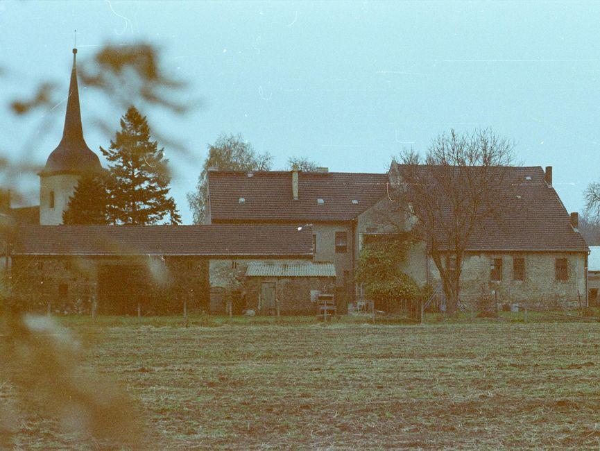 [Das Farbnegativ zeigt eine Aufnahme eines vermeintlichen kleinen Gutshofs, bestehend aus zwei in Verbund gebauten Wohnhäusern sowie einem länglichen Flachbau. Den größten Bildanteil nimmt ein brachliegender Acker ein, über den Hinweg das Grundstück fotografiert wurde. Im Hintergrund ist ein Kirchturm.]
