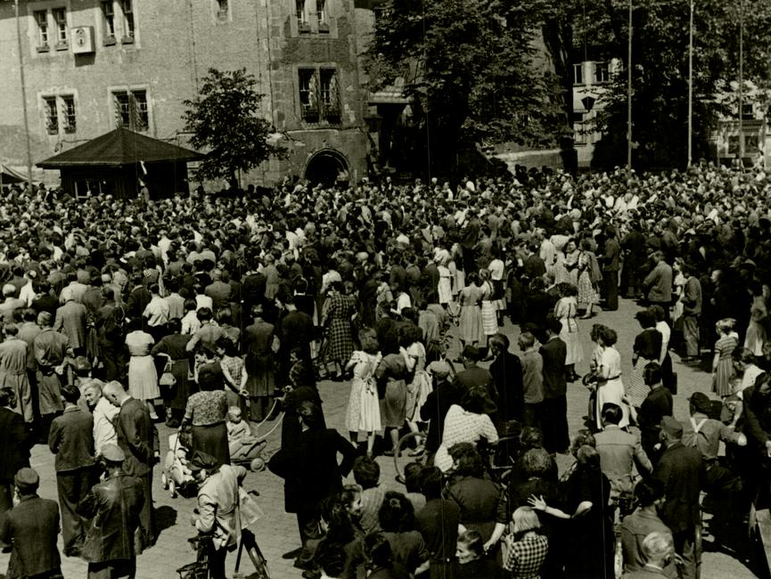Der Marktplatz im thüringischen Sömmerda am 17. Juni 1953 mit einigen hundert Menschen. Im Hintergrund ist das Rathaus zu sehen. Auf der Rückseite des Fotos ist handschriftlich vermerkt: 'Sömmerda am 17.6.53 – Marktplatz mit Rathaus und Vorplatz.'