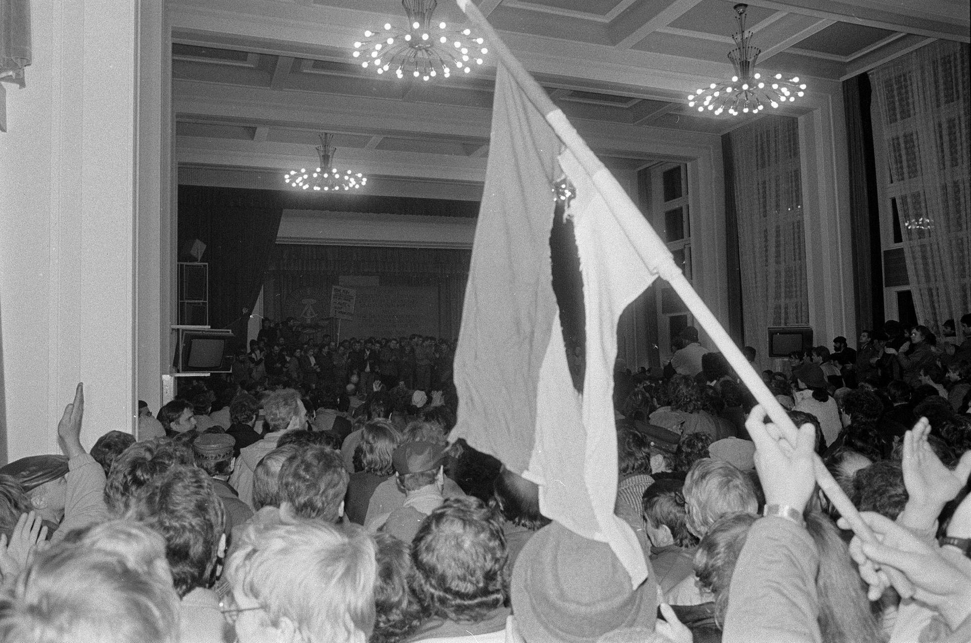Das Bild zeigt eine große Menschenmenge in einem großen Saal. Im Vordergrund schwenkt jemand eine nicht genau zu identifizierende Fahne.