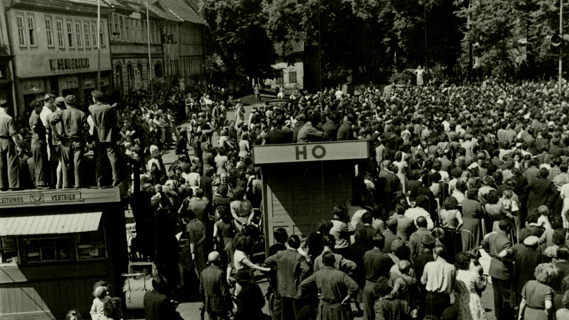 Der Marktplatz des thüringischen Sömmerda am 17. Juni 1953: Im Hintergrund die Menschenmenge, die anscheinend einer Kundgebung beiwohnt. Im Vordergrund die Bretterbuden 'Zeitungsvertrieb' und 'HO, auf denen Menschen sitzen oder stehen. Ganz vorne weitere Menschen, manche von ihnen mit Fahrrädern. Auf der Rückseite des Fotos ist handschriftlich vermerkt: 'Sömmerda am 17.6.53 – Demonstranten auf dem Marktplatz in Sömmerda (Rheinmetall).