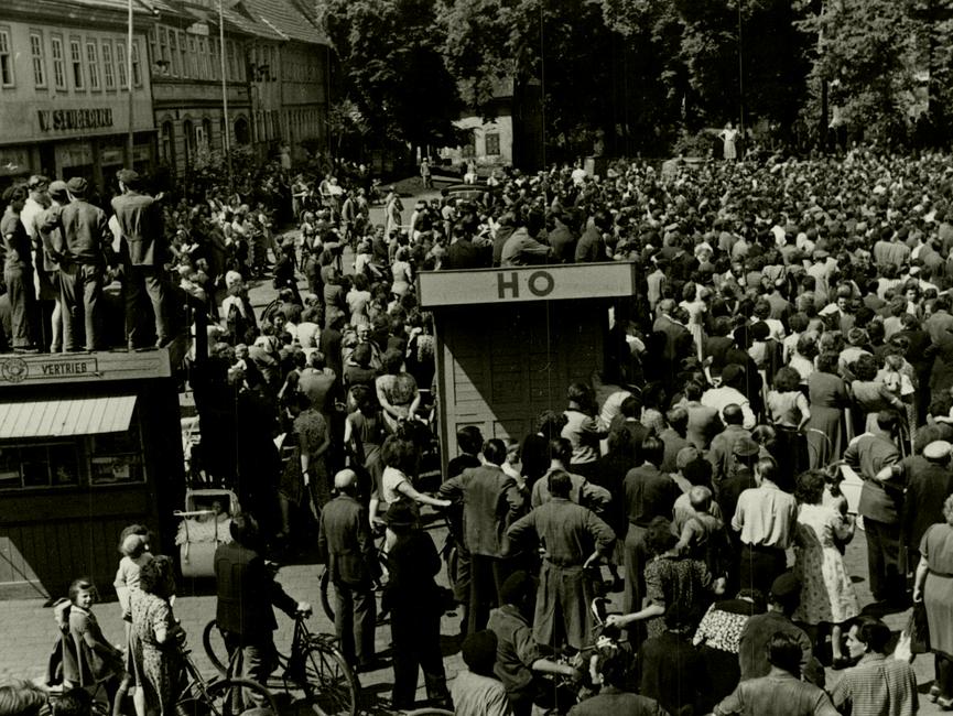 Noch einmal der Marktplatz des thüringischen Sömmerda am 17. Juni 1953. Im Hintergrund die Menschenmenge, die anscheinend einer Kundgebung beiwohnt. Im Vordergrund die Bretterbuden 'Zeitungsvertrieb' und 'HO, auf denen Menschen sitzen oder stehen. Ganz vorne weitere Menschen, manche von ihnen mit Fahrrädern.
