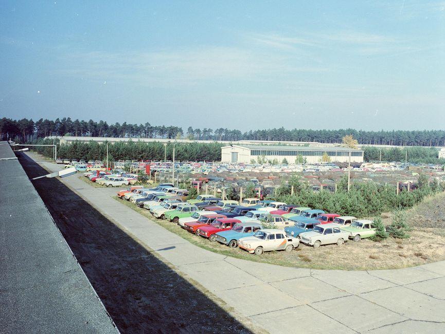 Das Bild, das vom Dach einer Lagerhalle aus fotografiert wurde, zeigt Autos in mehreren Reihen. Dahinter befindet sich eine weitere Lagerhalle.