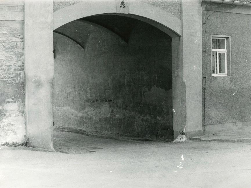 [Das schwarzweiße Lichtbild zeigt den Blick in eine Durchfahrt, an dessen Wand die Losung 'Wir wollen Reformen!' mit schwarzer Farbe angebracht wurde.]