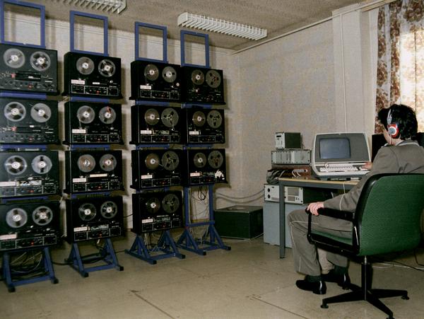 [Auf dem farbigen Lichtbild ist ein Mann im Bürostuhl sitzend von hinten zu erkennen. Bekleidet mit einer gräulichen Uniform sitzt er seitlich an einem Schreibtisch, auf dem ein Computer steht, der Bildschirm ist schwarz. Er trägt Kopfhörer. In seiner Blickrichtung stehen vier blaue Metallständer, auf denen jeweils vier Tonbandgeräte Platz haben.]
