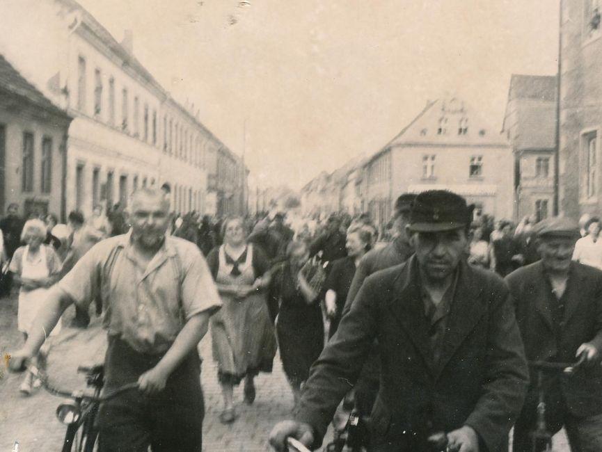Es handelt sich hierbei um eine Aufnahme von Demonstranten auf einer öffentlichen Straße, welche alle in die selbe Richtung laufen. Im Vordergrund schieben drei Demonstranten ihr Fahrrad. Der Großteil ist jedoch zu Fuß unterwegs.