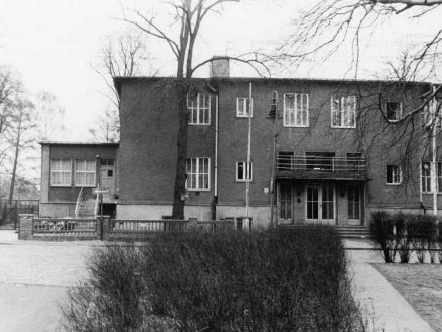 Das schwarz-weiße Lichtbild zeigt ein doppelstöckiges Haus mit Flachdach von vorn. An der linken Seite befindet sich ein kleiner Anbau, dessen Eingang höher gelegen ist als die vier Eingangstüren des Haupthauses.