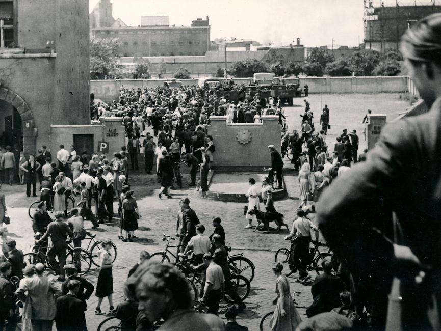 Erstürmung der Bezirkspolizei-Behörde in Magdeburg. Eine Menschenmenge steht vor dem Gebäude und der Ausfahrt der Behörde. Viele der Menschen haben Fahrräder dabei.