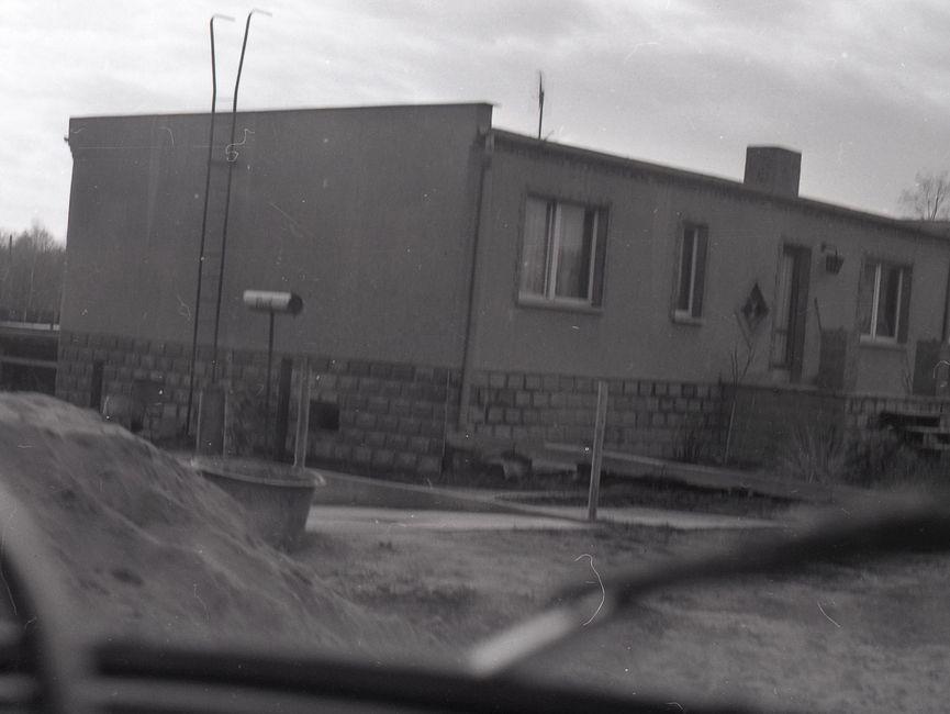 [Die Fotografie ist schwarz-weiß. Durch die Windschutzscheibe eines Fahrzeuges wurde ein einstöckiges Haus fotografiert. Das Haus besitzt an der linken Seite eine Leiter, die auf das Flachdach führt. Hinter dem Haus sind Bäume zu erkennen. Bei dem Haus könnte es sich um das rechte Gebäude von Bild 25 handeln. Im Vordergrund sind unscharf ein Sandhaufen und ein Maurertrog zu erkennen.]