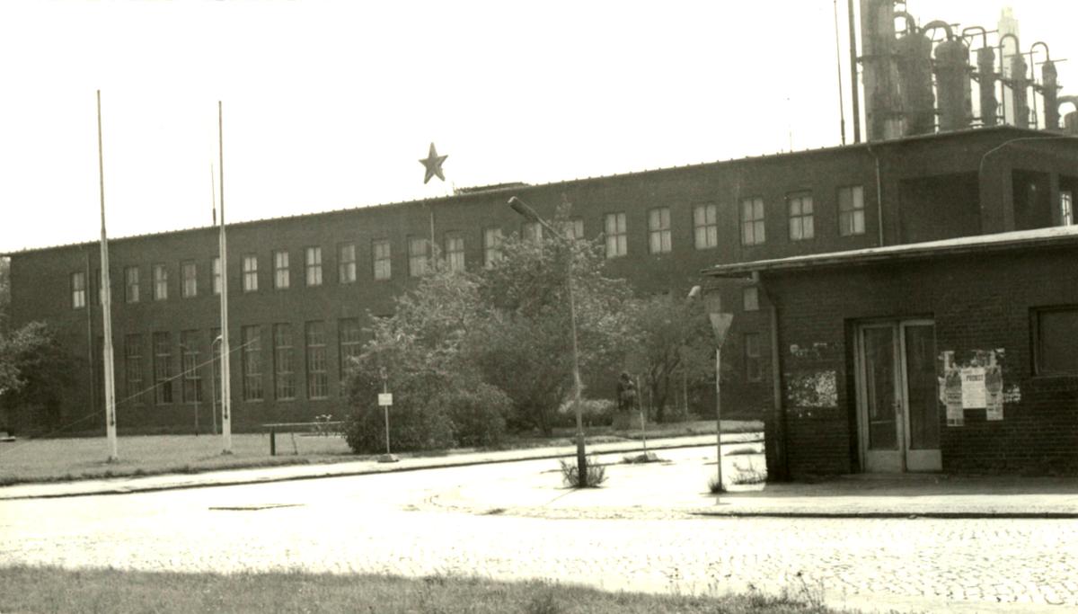 Das schwarz-weiße Lichtbild zeigt einen zweistöckigen Backsteinbau. Auf dem Dach ist mittig ein fünfzackiger Stern aufgestellt, auf der Grünfläche davor sind zwei leere Fahnenmasten zu sehen. Im Vordergrund ist eine T-förmige Kreuzung aus Kopfsteinpflaster.
