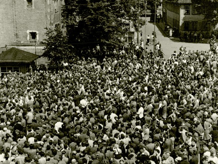 Der Marktplatz von Sömmerda am 17. Juni 1953. Eine große und dichte Menschenmenge ist zu sehen, die sich auf dem Marktplatz drängt. Im Hintergrund ist der Rathausvorplatz zu sehen, der noch weitestgehend ohne Menschen ist.