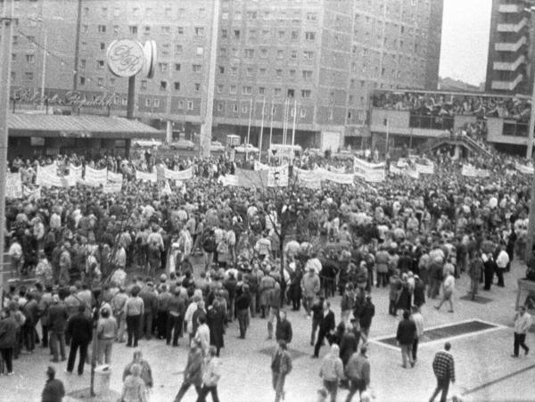 Foto, aufgenommen von einer erhöhten Position, von einem Demonstrationszug. Die Demonstranten tragen mehrere Transparente mit nicht zu erkennenden Aufschriften mit sich. Am Rand der Demonstration hat sich eine Gasse von Schaulustigen gebildet.