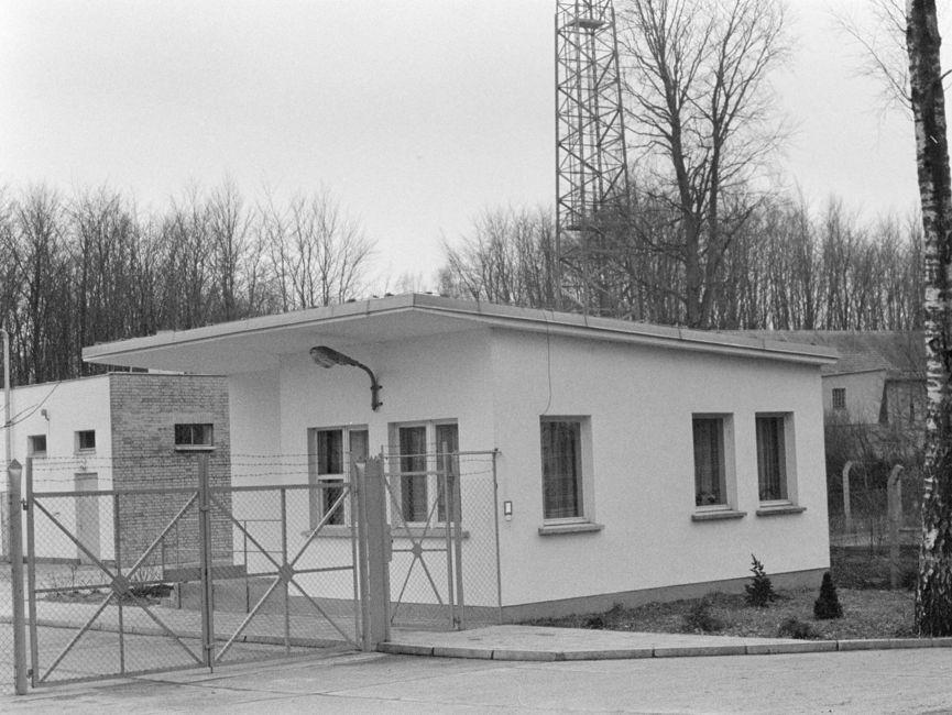 Dieses schwarz-weiße Lichtbild zeigt einen hellen Bungalow auf einem eingezäunten Grundstück, das zusätzlichen mit Stacheldraht geschützt wird. Im Hintergrund ist ein Funkmast erkennbar.