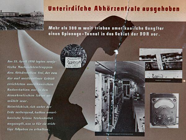 Unterirdische Abhörzentrale ausgehoben  Mehr als 300 m weit trieben amerikanische Gangster einen Spionage-Tunnel in das Gebiet der DDR vor.  Am 22.April 1956 legten sowjetische Nachrichtentruppen den Abhörstollen frei, der von der auf westberliner Gebiet errichteten amerikanischen Radarstation aus in den demokratischen Sektor gewühlt war. Heimtückisch, sich unter der Erde verbergend, hatten amerikanische Spione Telefonkabel angezapft, um so für sie wichtige Angaben zu erhalten.  [Der Hintergrund des vermeintlichen Flugblattes ist der Umriss eines alten Telefonhörers sowie kleine schwarz-weiße Aufnahmen aus dem Tunnel zu sehen. Es verläuft eine vertikale Risskante.]
