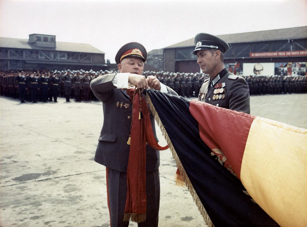 [Das farbige Lichtbild zeigt im Vordergrund Erich Mielke in voller Uniform, wie er ein rotes Ehrenbanner an den quer gelegten Fahnenmast oberhalb der Flagge der DDR knüpft. Neben ihm steht ein Mann, ebenfalls in voller Uniform. Im Hintergrund salutiert das Wachregiment 'Feliks E. Dzierzynski' vor zwei lang gestreckten, flachen Häusern die gemeinsam eine Ecke bilden.]