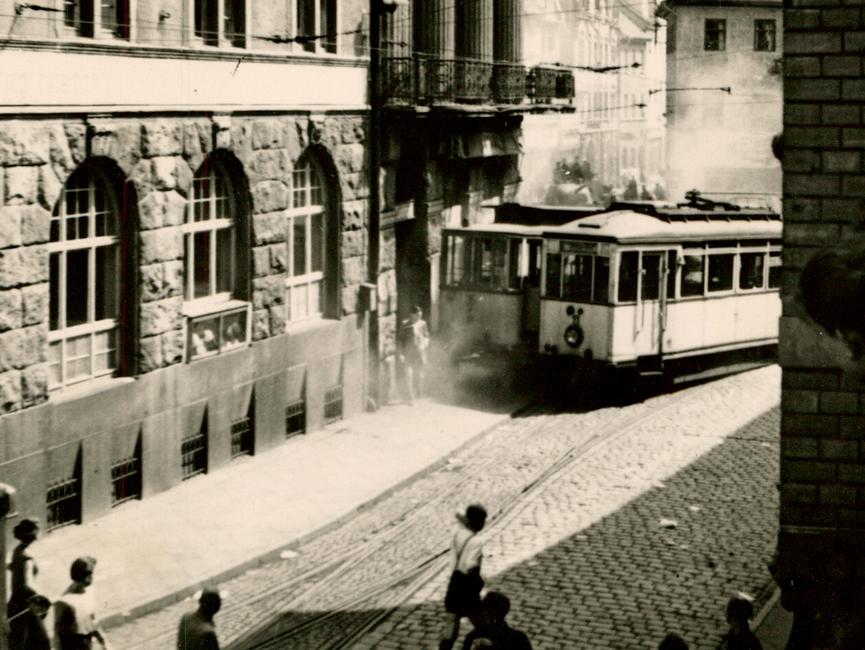 Auf einer Straße stehen zwei Straßenbahnwagen, von denen einer neben den Schienen steht.
