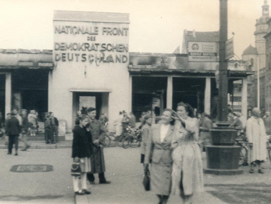 Menschen vor dem ausgebrannten Pavillon der Nationalen Front in Leipzig.