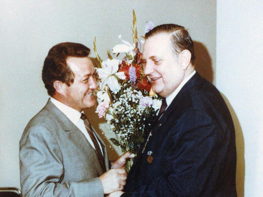 Heinz Volpert und Alexander Schalck-Golodkowski reichen sich lächelnd die Hände. Heinz Volpert hält in seiner linken Hand einen großen Blumenstrauß.