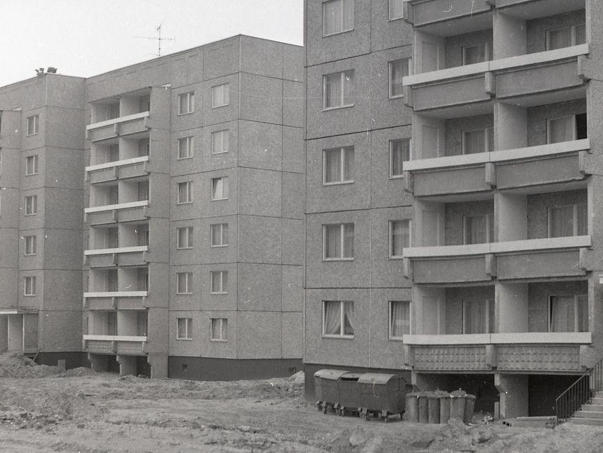 [Die schwarzweiße Negativaufnahme zeigt anteilig zwei sechsstöckige Plattenbauten, vermtulich vom Wohnbauserientyp 70. Sie scheinen bereits bewohnt zu sein, da in allen sichtbaren Fenstern Gardinen hängen. Vor den Wohnhäusern stehen mehrere Mülltonnen aus Metall. Die angrenzenden Freiflächen vor und zwischen den beiden Häuserblocks wirken baustellenartig, Furchen ziehen sich durch das Sand-Geröll-Gemisch. In der unteren rechten Bildecke ist eine große liegende Kabeltrommel.]