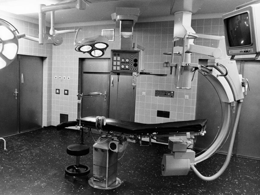 Das Schwarz-Weiß-Bild zeigt einen Operationssaal im Stasi-Krankenhaus Berlin-Buch. In der Mitte des raumes befindet sich eine Liege, rechts daneben ein großes technisches gerät, wahrscheinlich ein Computertomograph. Außerdem befinden sich zwei große Leuchten im Raum.