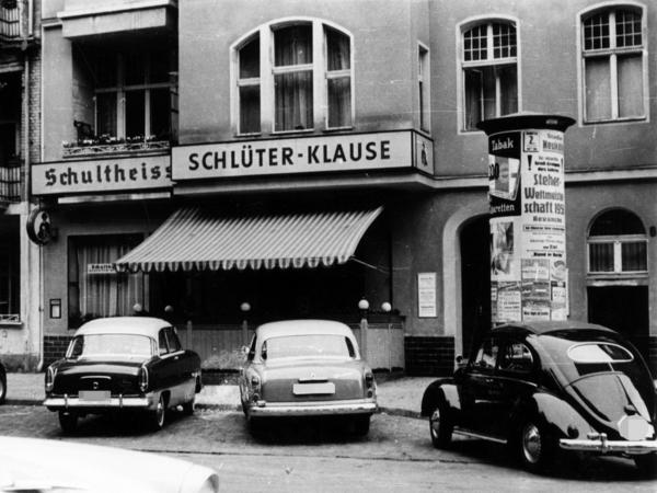 Das Schwarz-Weiß-Bild zeigt ein Lokal am Kurfürstendamm in West-Berlin. Davor parken einige Autos.