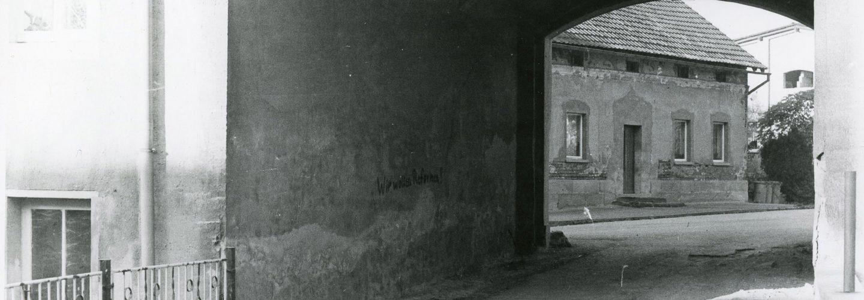 [Aufnahme von der anderen Seite der Hofdurchfahrt, die Losung 'Wir wollen Reformen!' in schwarzer Schrift ist nun auf der linken Seite. Die durchführende Straße wirkt schmal und sehr ausgefahren aufgrund diverser Schlaglöcher. Es handelt sich um ein Schwarzweiß-Foto.]
