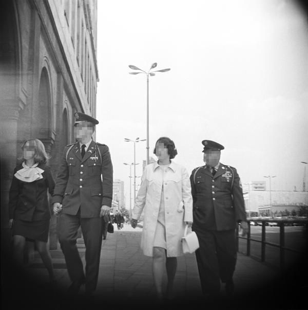 [Zu sehen ist ein schwarz-weißes Negativ, das im Mittelpunkt zwei Mitglieder der US-Armee in Uniform mit ihren weiblichen Begleitungen zeigt. Sie gehen dem Fotografierenden zugewandt über einen breiten Gehweg. Das Bild ist an den Ecken verdunkelt, was den Eindruck erweckt, dass die Kameralinse bei der Aufnahme hinter einem runden Ausschnitt verborgen war.]