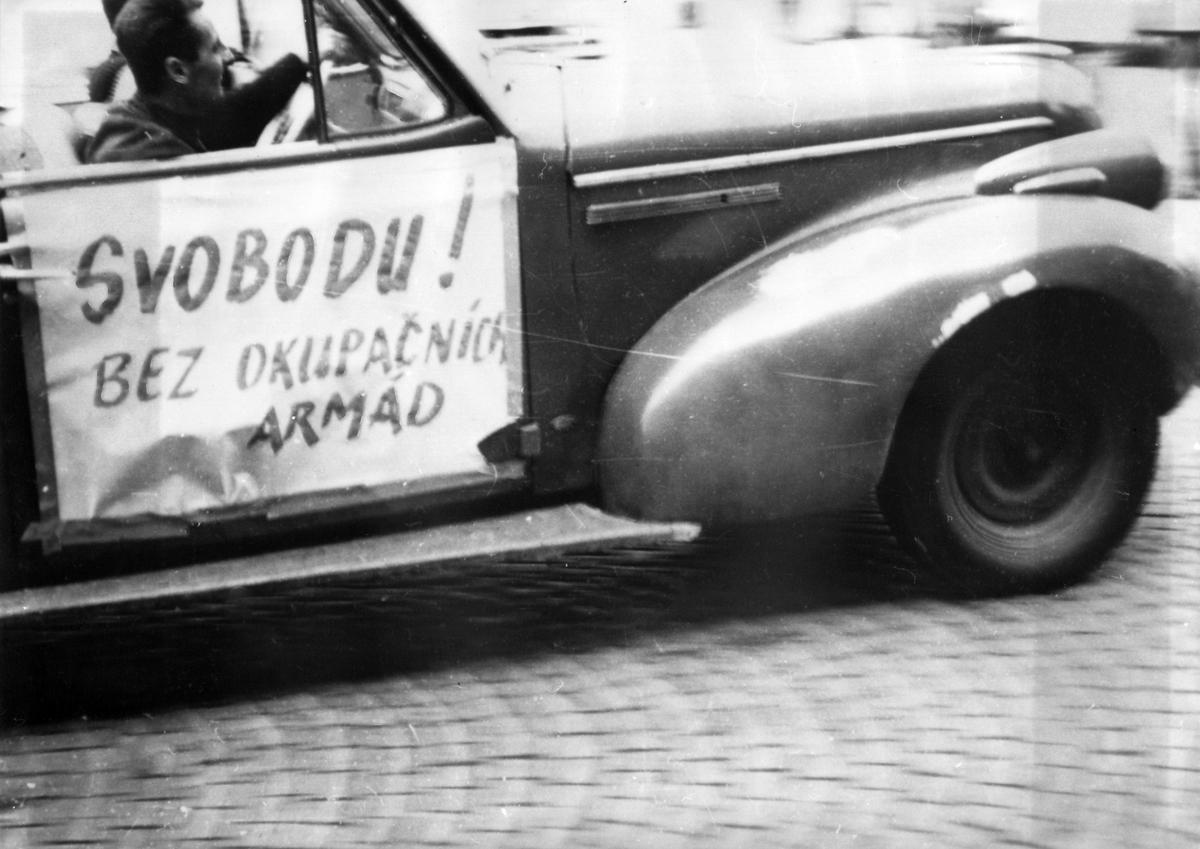 Das Schwarz-Weiß-Foto zeigt den vorderen, seitlichen Teil eines Autos. Im Auto selbst sitzen zwei Personen. An der Beifahrertür ist ein Plakat angebracht, auf dem 'Svobodu! bez Okupacních armád' steht.