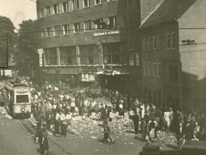 Auf dem Holzmarkt in der Jenaer Innenstadt befinden sich mehrere Menschentrauben, die sich um zwei Panzer ringen. Am linken Bildrand sieht man einen der Straßenbahnwagen, mit denen die Jenaer Bürgerinnen und Bürger den Weg der sowjetischen Panzer blockierten.