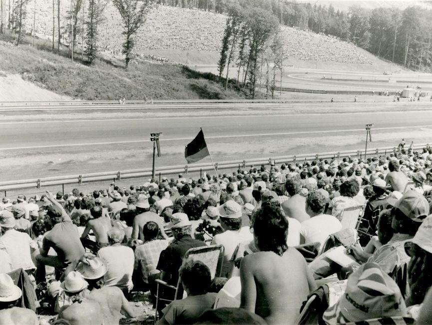 Das Bild zeigt eine Zuschauertribüne und einen Teil der Rennstrecke des Automodroms Brünn. In der Mitte des Bildes schwenkt ein Mann eine schwarz-rot.goldene Fahne.
