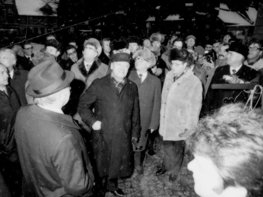 Diese Schwarzweißaufnahme zeigt Helmut Schmidt und Erich Honecker in der Mitte des Bildes bei der Besichtigung des Marktplatzes und des Doms in Güstrow. Um die Beiden herum haben sich einige Menschen versammelt. Darunter offenbar auch Reporter, die ihre Mikrofone auf Helmut Schmidt und Erich Honecker richten. Einige Zuschauer und Erich Honecker blicken vom Betrachter aus gesehen nach links oben.