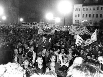 [Zu sehen ist eine Menschenmenge auf einem schwarzweißen Lichtbild. Es sind auch einige Transparente und Plakate mit politischen Forderungen.]