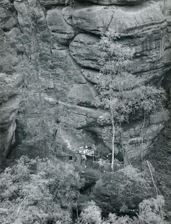 Das Bild ist eine Schwarz-weiß-Fotografie der sogenannten Fernblick-Boofe im Kreis Sebnitz aus einiger Entfernung. Zu sehen ist vor allem eine massive Felswand, die von Spalten durchzogen und teilweise mit Bäumen bewachsen ist. Im unteren Drittel des Bildes ist an den Fels angebaut die Holzverkleidung der Boofe erkennbar.