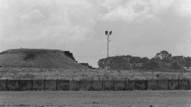 Das Schwarz-Weiß-Bild zeigt einen Teil eines umzäunten Bunkers. Dieser ist mit Gräsern bewachsen. In der Bildmitte im Hintergrund befindet sich ein Turm mit Kommunikationsanlagen. Die Umzäunung besteht aus einer Mauer mit aufgesetztem Stacheldraht.