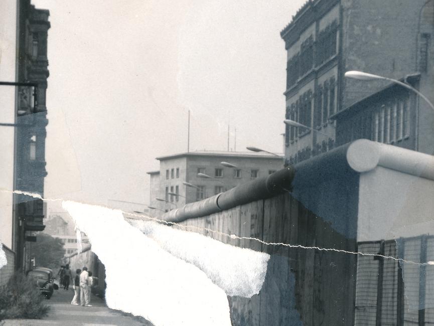 Auf dem schwarz-weiß Lichtbild ist der Blick auf die Berliner Mauer von der Westseite der Stadt dokumentiert. Die mit Grafitti versehenen Mauerelemente werden im Bildvordergrund von einem Metallgitterzaun abgelöst. Das Foto war mehrfach zerrissen worden und konnte nur anteilig manuell rekonstruiert werden.