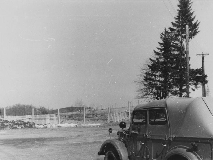 Ein Pkw befährt ein Gelände. Im Hintergrund befinden sich rechts einige Nadelbäume und in der Mitte ein nicht durchgängiger Zaun.