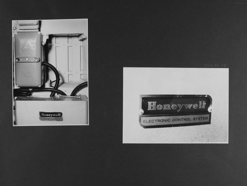 [Bild 1: Ein Kunststoffgehäuse, aus dem ein schwarzer Schlauch tritt, dessen Windungen im Hintergrund zu erkennen sind, hängt über einem Metallkasten mit dem Markenschild 'Honeywell'.]  [Bild 2: Nahaufnahme des Markenschildes:  Honywell Electronic control system]